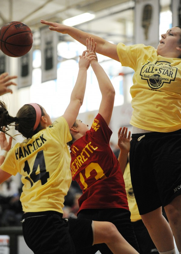 The West's Sydney Hancock (left) and Marquis MacGlashing (right) put a stop to the East's Chandler Guerette as she attempts a jump shot during the class A/B McDonald's All-star basketball game at Husson University on Saturday. The East won 119-66.