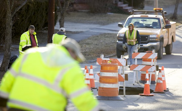 Bangor Public Works employees fill a sinkhole Monday morning that formed on Lincoln Street over the weekend.
