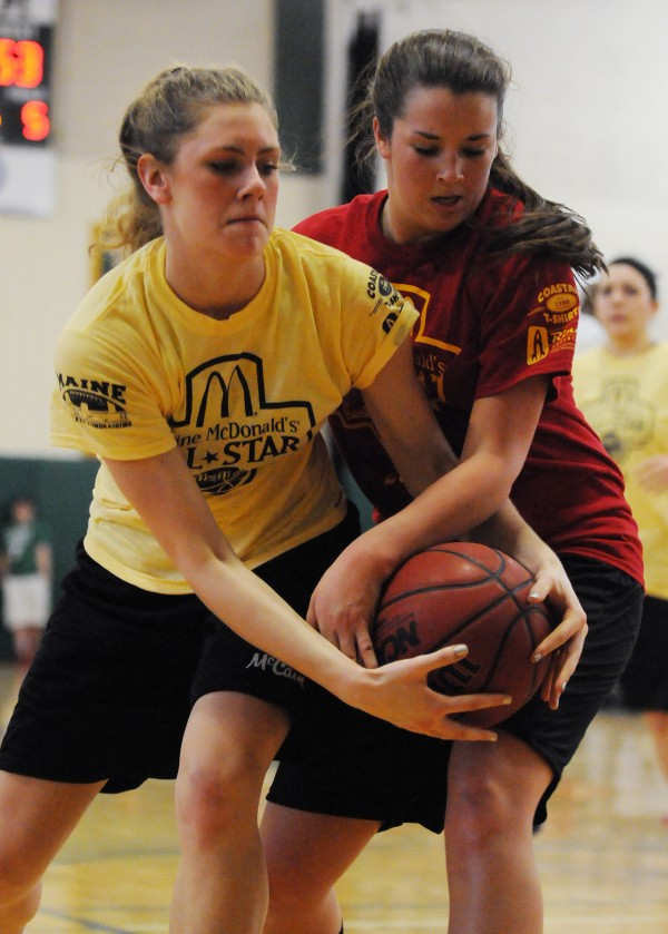The West's Kelsey Winslow ties up the ball with the East's Gabby Foy during the class A/B McDonald's All-star basketball game at Husson University on Saturday. The East won 119-66.