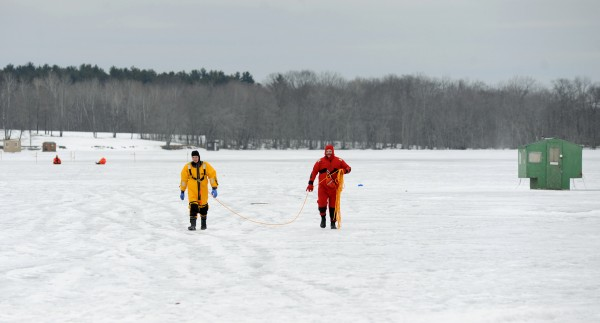 Hermon firefighters Byron Ouellette (left) and Corey Tibbetts walk off of frozen Hermon Pond after marking off an area of thin ice where a pick up truck went through.  Robert Sinclair of Glenburn, who was on the pond to get his ice shack, was able to get out of his truck before it went under and sank about 12 feet.