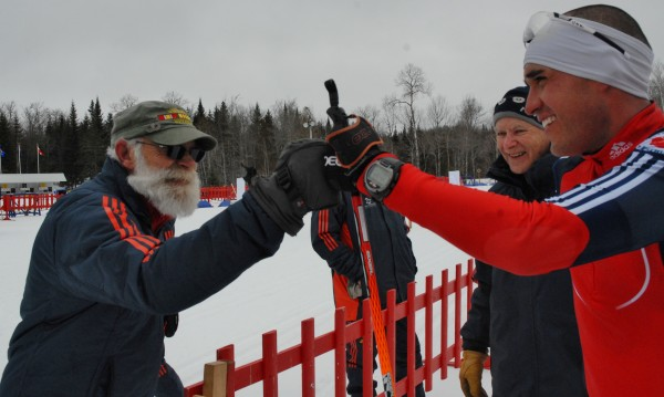 Fort Kent biathlon volunteer Alan Thibodeau (left) shares a fist-bump with Paralympic skier Omar Bermejo after Sunday's 15K mass start race at the 10th Mountain Lodge. Thibodeau was partnered with Bermejo over three days of competition assisting with scoring, logistics and even offering some coaching tips to the skier who lost his right arm after a motorcycle accident two years ago.