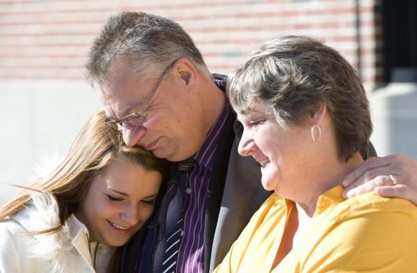 Lexi Henkel (from left) gets a hug from her father, Norbert, as they and Lexi's mother, Judy, talk to the media outside the Penobscot Judicial Center in Bangor on Tuesday.