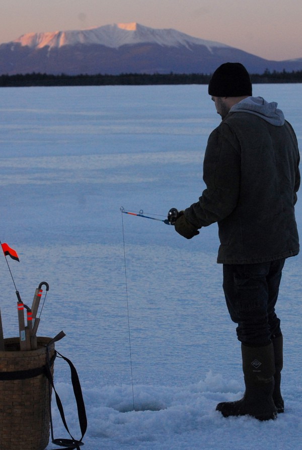 Nick Elliott, of Corinth, puts a jigging stick to work at Upper Jo Mary Lake, in hopes of picking up some cusk Saturday evening on March 9, 2013. Mount Katahdin looms in the background.