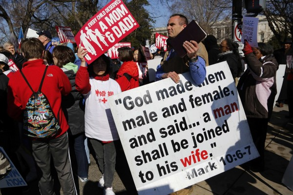 Anti-gay protesters hold signs outside the U.S. Supreme Court, which heard arguments March 26, 2013,on a case to lift California's ban on same-sex marriage.
