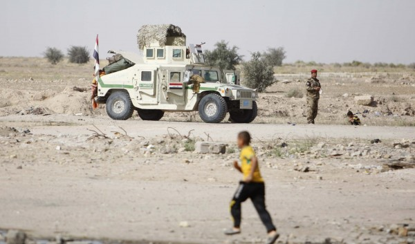 An Iraqi soldier stands guard near an armoured vehicle at Um Qassr near Iraq-Kuwait border, March 14, 2013.