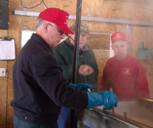 George Bradbury (left) and Boyd Bradbury (right, in red) operate the evaporator for producing maple syrup at Bradbury Maple Farms in Bridgewater on Sunday, March 24, 2013.