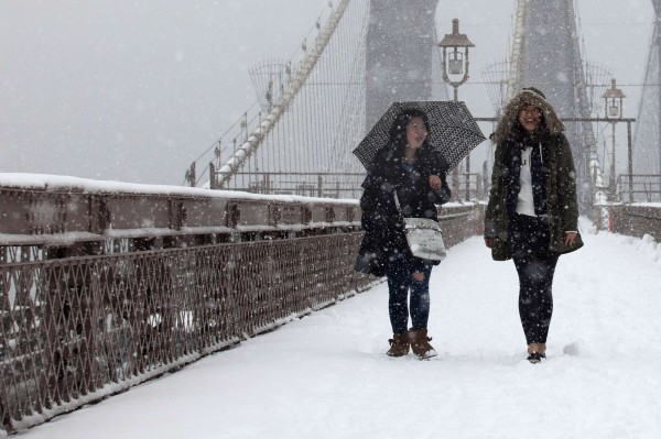 Women walk on the Brooklyn Bridge during a snowstorm in New York on Friday.
