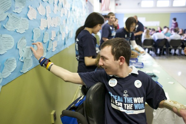Brewer student Zac Burnham, 18, tapes an &quotR-word&quot pledge to a wall in the school's cafeteria. Brewer High School is sponsoring a campaign to replace the term mental retardation with intellectual disability.