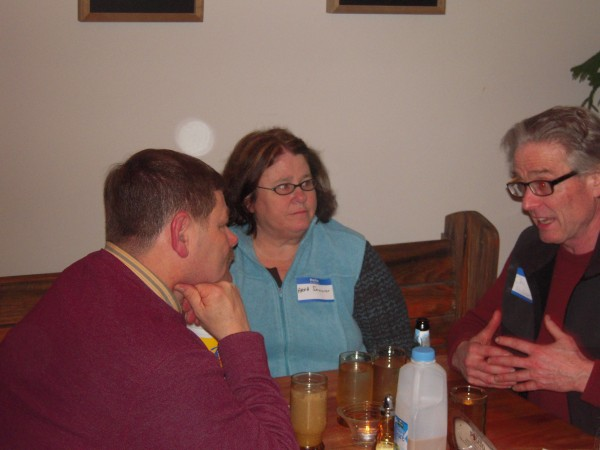 Chris Hallweaver of Northern Girl vegetable processing in Limestone (right) makes a point in a conversation with Rep. Bob Saucier, a member of the Legislature's Agriculture, Conservation and Forestry Committee, and his wife Anna of Presque Isle.
