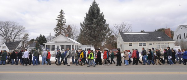 People walk along North Main Street in Brewer during the Way of the Cross procession Sunday. The procession started at St. Joseph's Catholic Church in Brewer, and participants walked about two miles to St. John's Catholic Church in Bangor. Portraying Jesus in the procession is Justin Vroom.