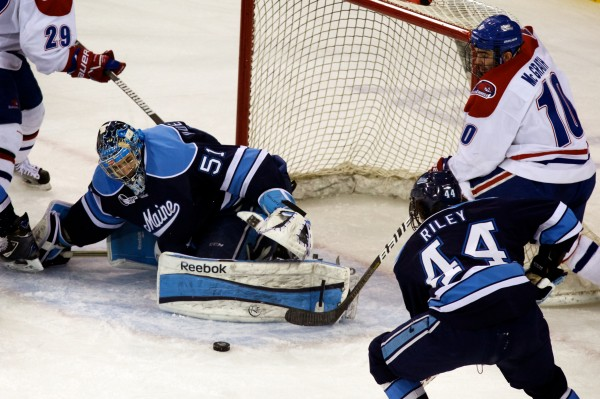 University of Maine's Martin Ouelette defends the goal against UMass Lowell's Ryan McGrath (right) while Maine's Conor Riley defends in the first period Thursday night, March 14, 2013, in Hockey East quarterfinal action in Lowell, Mass.