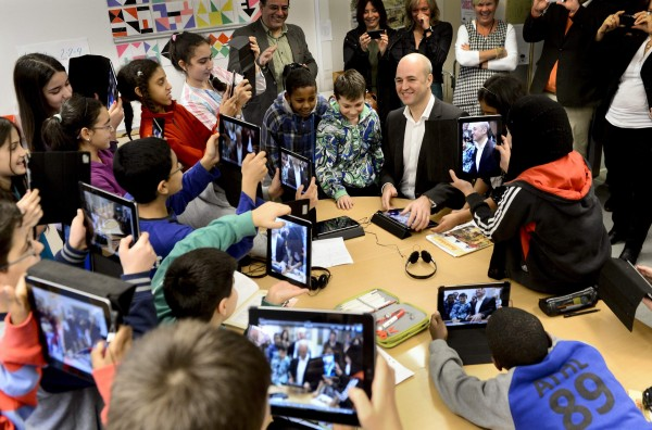 Fifth graders use their iPads to take photos of Sweden's Prime Minister Fredrik Reinfeldt (center) during his visit to Husby School, west of Stockholm, November 21, 2012.