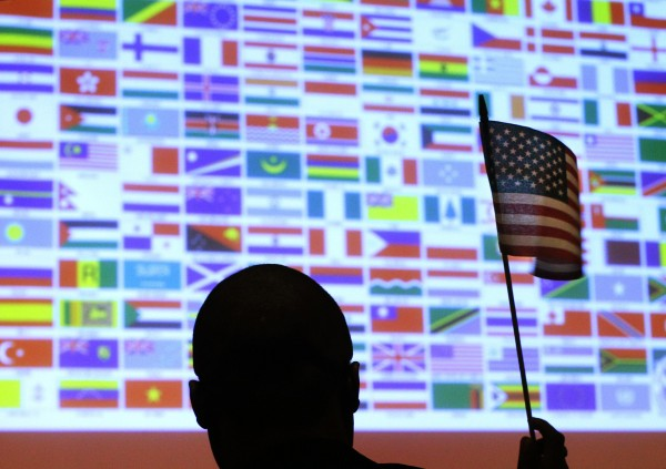 A new U.S. citizen waves a U.S. national flag in front of a display of flags of the more than 40 nations represented by the more than 90 immigrants becoming U.S. citizens during a naturalization ceremony at Boston College in Chestnut Hill, Mass., on March 21, 2013.