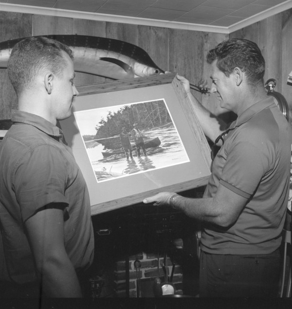 Boston Red Sox great and Major League Baseball Hall of Famer Ted Williams (right) admires a painting by Tom Hennessey of the Bangor Daily News. The painting depicts Williams on one of his Atlantic salmon fishing trips to Canada's Miramichi River. Hennessey presented the work to Williams in Bangor on Sept. 4, 1965.