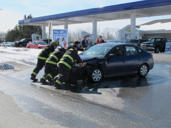 Firefighters from Ellsworth Fire Department push a damaged Hyundai Elantra out of the street on Thursday morning. The Hyundai's driver was pulling out of the Irving gas station, pictured, when it was struck by a pickup truck.