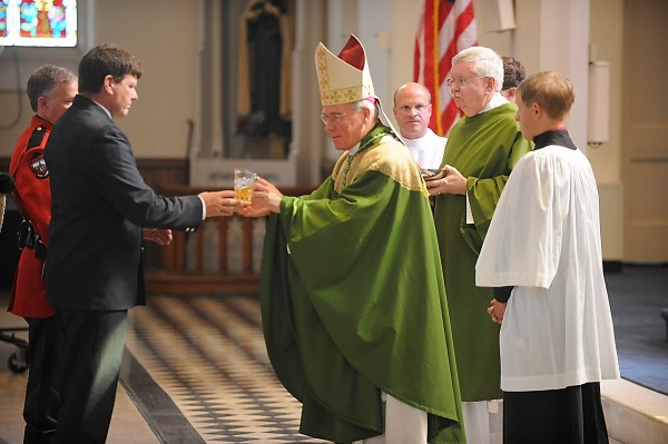During the Liturgy of the Eucharist, Warden Phil Richter (from left) and Bangor firefighter John Higgins were among the gift-bearers to Bishop Richard J. Malone during Sunday's Blue Mass at St. John Catholic Church in Bangor.
