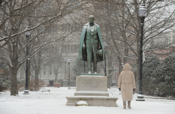 A pedestrian walks past the statute of Hannibal Hamlin while light snow falls on downtown Bangor on Tuesday.