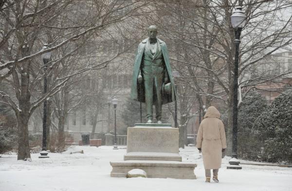 A pedestrian walks past the statute of Hannibal Hamlin while light snow falls on downtown Bangor on Tuesday.