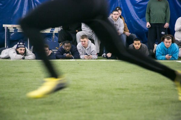 Spectators clock prospects on their phones as they go through drills at the University of Maine's NFL Pro Day workouts on Wednesday, March 20, 2013.