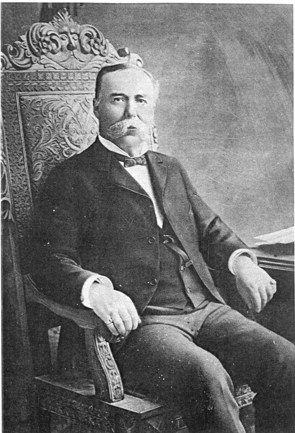 """Flavius O. Beal shows off his """"big diamond"""" while seated in the """"big oak chair""""."""