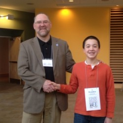 Brandon Aponte, 12 of Brooklin (left) is congratulated Saturday by head judge Michael Ashmore on winning the Maine State Spelling Bee.