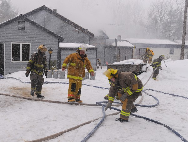 Firefighters battle a house fire on Alley Lane in Troy Monday afternoon. Fire crews from Troy, Unity, Dixmont and Detroit responded to the call.