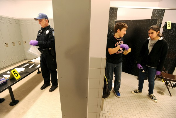 Veazie police Officer Roger Hershey (left) gets evidence bags ready for Jack Dalton and Kaylyn Larkin (right), who were assigned the role of evidence technicians in Thursday's mock crime scene at the Veazie Community School. Jack has found some evidence in the trash can. The &quotcrime&quot being investigated is a robbery at a tattoo parlor (the girls locker room) where illegal card games were being played after hours and money was stolen.