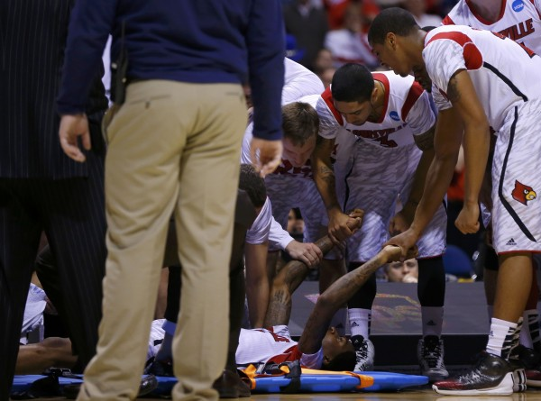 Louisville Cardinals players hold hands with Kevin Ware (5) after he broke his leg in the first half against the Duke Blue Devils during their Midwest Regional NCAA men's basketball game in Indianapolis on Sunday, March 31, 2013.
