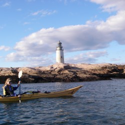 Andrea Reny of Round Pond paddles past Moose Peak Light on Mistake Island. The 72-foot lighthouse marks the entrance to Main Channel Way and Eastern Passage near Beals Island.