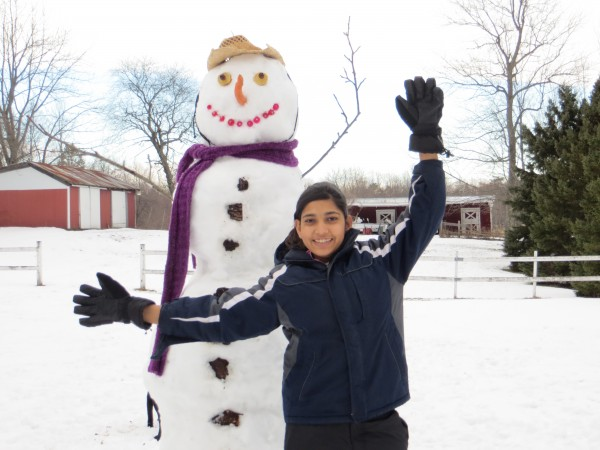 Aqsa Munir, an exchange student from Pakistan spending the year in Hampden, Maine poses with her first-ever snowman.
