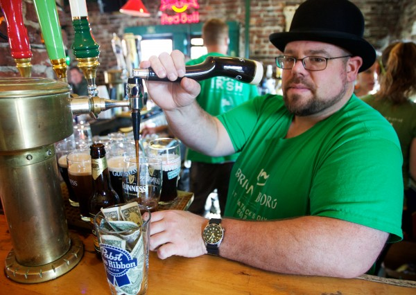 "Long-time bartender at the Brian Boru Publick House in Portland, Jeff Dalbec, pours multiple pints of Guinness at once Saturday morning,€"" St. Patrick's Day,€"" March 17, 2012."