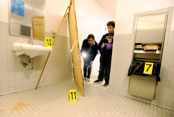 Seventh-grade students at the Veazie Community School investigate a mock crime scene on Thursday. Assigned the role of evidence technicians, Kaylyn Larkin (left) and Jack Dalton mark, log and collect evidence from the scene.  The &quotcrime&quot being investigated is a robbery at a tattoo parlor (the girls locker room) where illegal card games were being played after hours and someone has stolen the gambling money.
