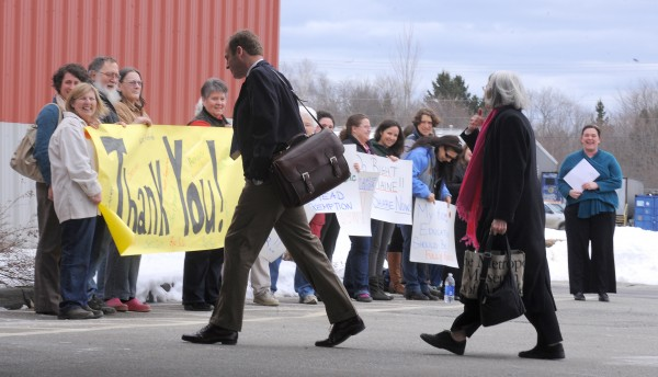 Maine State Reps. Mike Carey (foreground left) and Peggy Rotundo walk past a group lead by the Maine People's Alliance  expressing their opposition to the proposed budget cuts by Gov. Paul LePage at Jeff's Catering in Brewer on Tuesday.