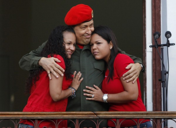 Venezuela's President Hugo Chavez hugs his daughters Rosa (left) and Maria while appearing to supporters on a balcony of Miraflores Palace soon after his return to the country from Cuba, where he underwent surgery and treatment for cancer, in Caracas in this July 4, 2011 file photo. Chavez has died after a two-year battle with cancer, ending the socialist leader's 14-year rule of the South American country, Vice President Nicolas Maduro said in a televised speech on March 5, 2013