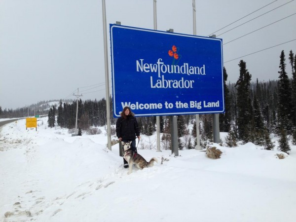 Karen Miles of Belfast posed outside of a road sign on her way north to Goose Bay, Labrador. From there, she and two others left Tuesday morning for a journey by dogsled hundreds of miles north to Nain, Labrador.