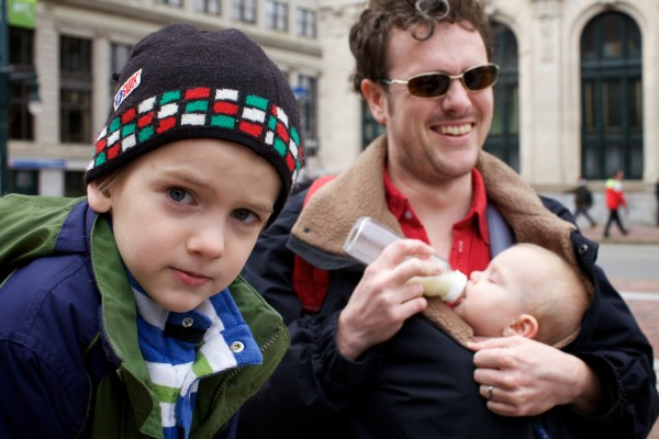 Eliot Gardella, 6, and his father, Kevin, holding baby Willow, said Wednesday they're in favor of the city's ban on smoking in public places Wednesday while hanging out in Monument Square.