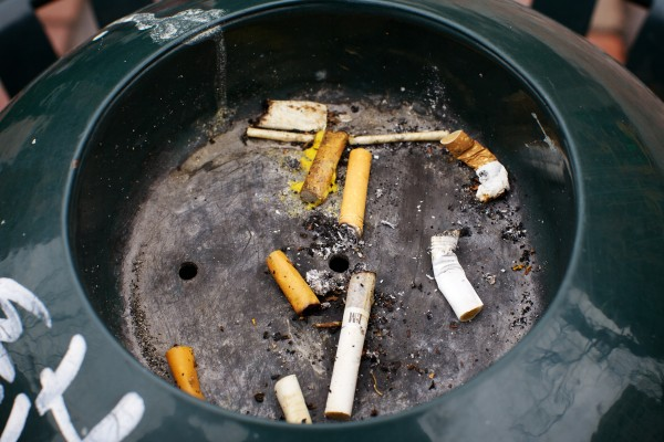 Cigarette buts grace an ashtray atop a trashcan in Portland's Monument Square on Wednesday. The city recently outlawed smoking in public spaces.