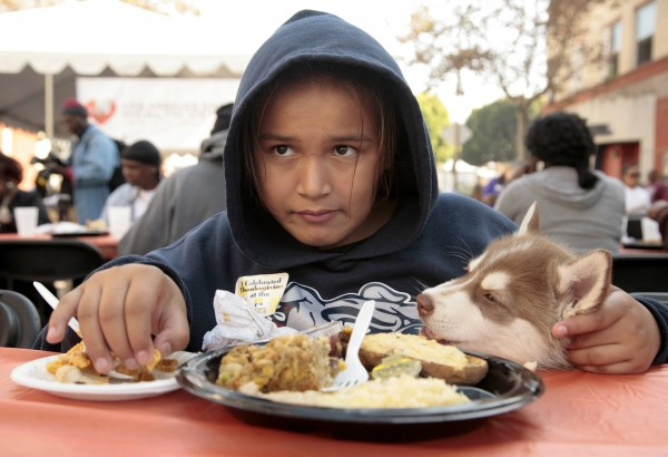 Donna Hernandez, 12, holds her puppy, Tommy, as she and her family eat a free Thanksgiving meal for the Skid Row homeless and needy  in Los Angeles, Calif., on Nov. 21, 2012.