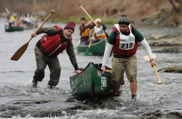 The team of Adam Vedoni and Dan Cassaday run through low water near the start of the 46th annual Kenduskeag Stream Canoe race on Saturday, April 21, 2012.