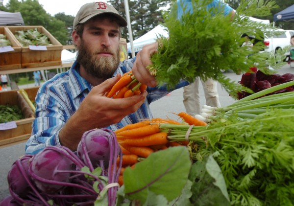 Gene Ripley of Ripley Farm in Troy replenishes his stand with fresh carrots at the Orono Farmers' Market on in July 2009. The farmers marker reopens for the season on May 4.