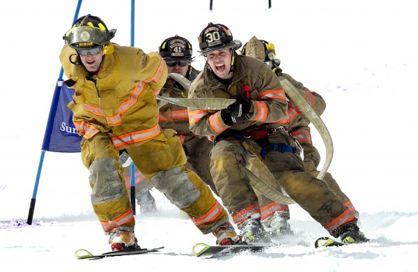 Kyle Demillo (30), of the Jay Fire Department, shouts encouragement to the leader Griffin Couture as they near the finish line in the 23rd annual Firefighters Race at Sunday River Ski Resort, Sunday, March 24, 2013, in Newry.
