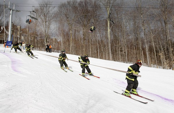 The team from Bethel stretches out as they carry a 50-foot-long hose while competing in the 23rd annual Firefighters Race at the Sunday River Ski Resort, Sunday, March 24, 2013, in Newry.