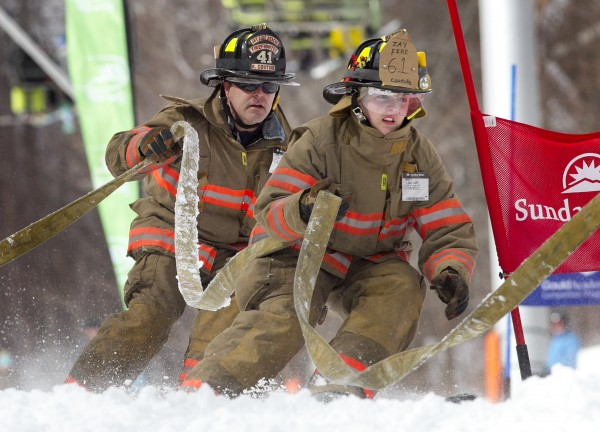 Like father, like daughter -- Casidee Couture and her dad, Rick Couture, carry the hose around a gate for the team from Jay while racing in the 23rd annual Firefighters Race at Sunday River Ski Resort, Sunday, March 24, 2013, in Newry.