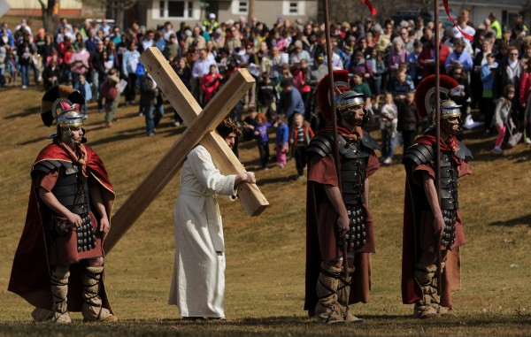 Tim Mullen dressed as Jesus, center, and surrounded by Roman soldiers walks to the 5th station of the cross at Indian Trail Park in Brewer, on Sunday, April 1, 2012, where Simon of Cyrene joins him to help him carry the cross.