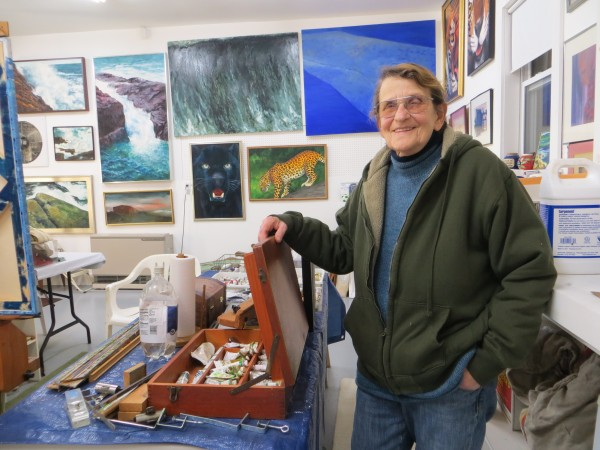 Joan Fenrow stands in her home art studio, surrounded by the tools of her trade and many of her paintings.
