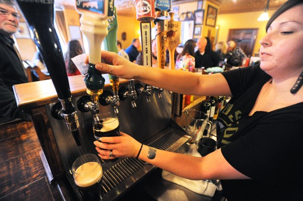 Jennifer Ghergia, a bartender at Paddy Murphy's pub in Bangor, pours a beer for a patron Thursday evening.