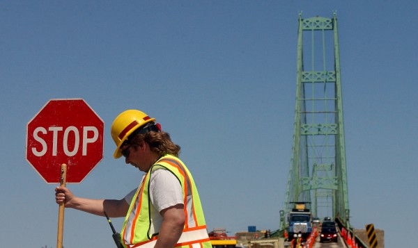 Scott Roy of J.D. Flagging directs traffic on the Deer Isle side of the Deer Isle - Sedgwick bridge in April 2007 as workers were making preparations to start replacing the concrete deck on the bridge.