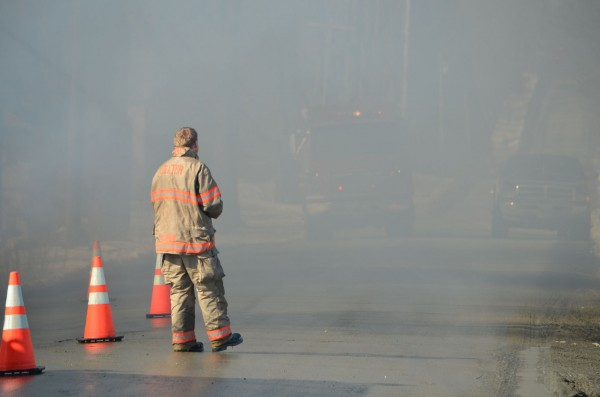 A fire tanker truck approaches a Dexter fire fighter through the smoke-filled Corinna Center Road in Corinna, the site of a barn fire on Thursday, March 21, 2013. Seven fire departments responded to the fire.