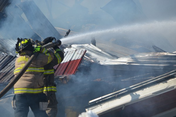 Two Corinna fire fighters attempt to douse flames on a barn fire at Simpson View Farms on Thursday, March 21, 2013.