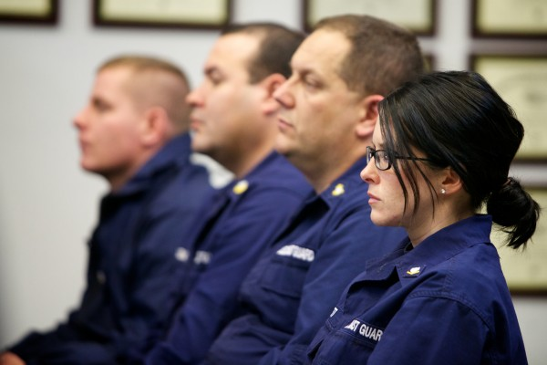Petty Officer Leah Brett listens as U.S. Secretary of Agriculture Tom Vilsack speaks at the South Portland Coast Guard station Thursday.
